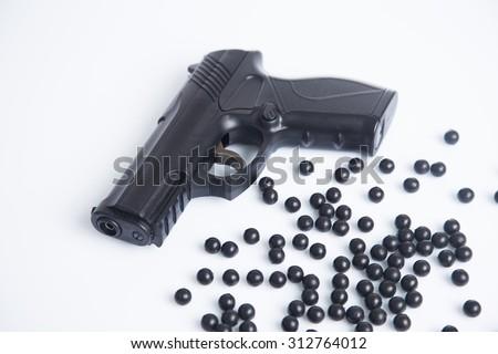 Gun and plastic balls - stock photo