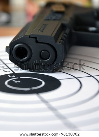 Gun and target, macro with small depth of field - stock photo