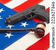 Gun and wooden judge gavel over USA flag - studio shoot - 1 to 1 ratio - stock photo
