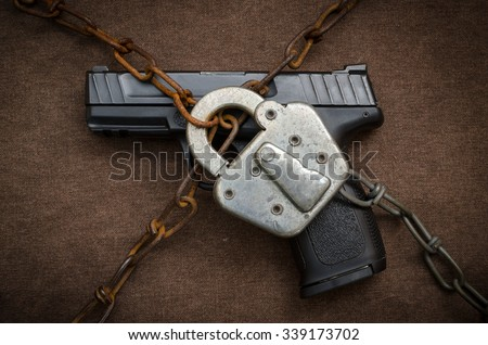 Gun Control Concept - Pistol behind Lock and Chain - stock photo