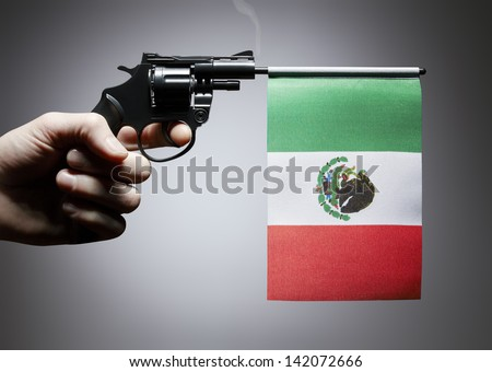 Gun crime concept of hand pistol showing the flag of mexico - stock photo