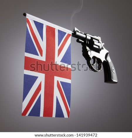 Gun crime concept of hand pistol showing the flag of united kingdom - stock photo