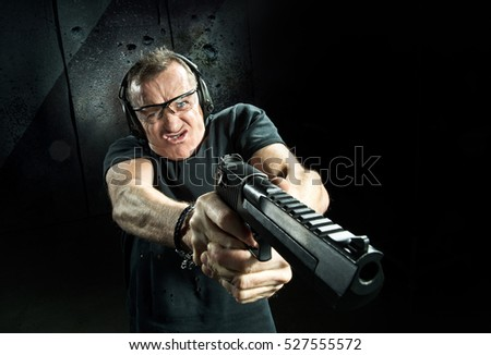 Gun in the hands of the crazy man in a headphones