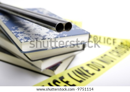 Gun on top of schoolbooks with police line tape. - stock photo