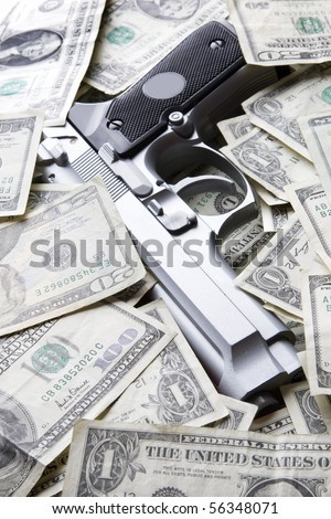 Gun placed on a pile of dollar bills - stock photo