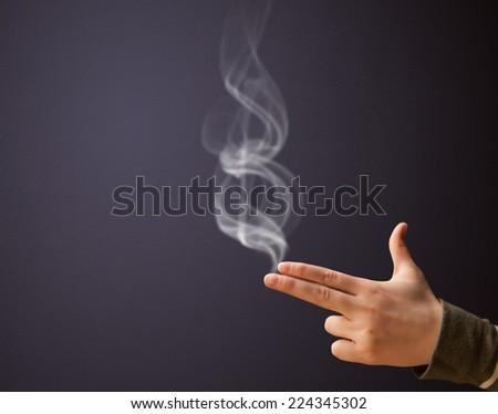 Gun shaped woman hand with smoke - stock photo