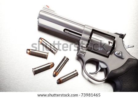 gun with bullets on steel surface - modern revolver handgun - stock photo