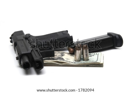 gun with slide back next to magazine and bullets, atop stack of money, isolated on white - stock photo