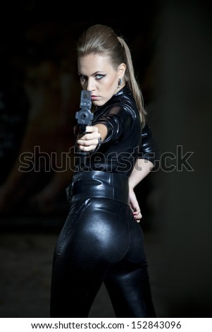 gun woman in leather suit over black  - stock photo