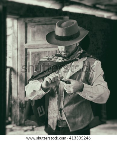 Gunfighter of the wild west while scrolling tobacco. - stock photo