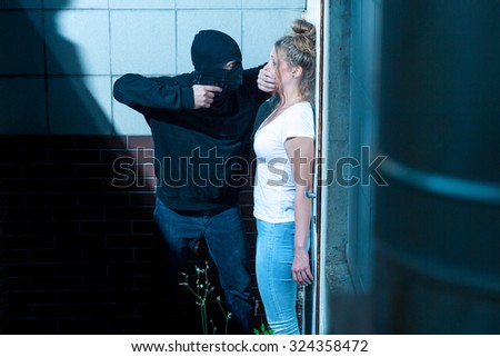Gunman is hushing young and scared woman - stock photo