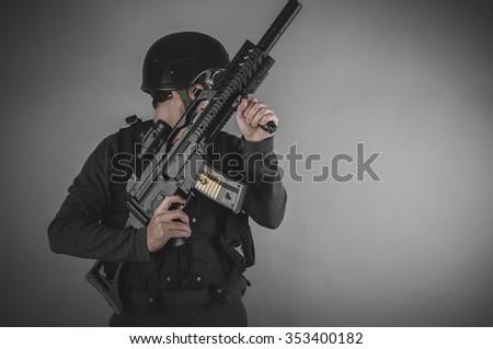 gunpowder, airsoft player with gun, helmet and bulletproof vest on gray background - stock photo