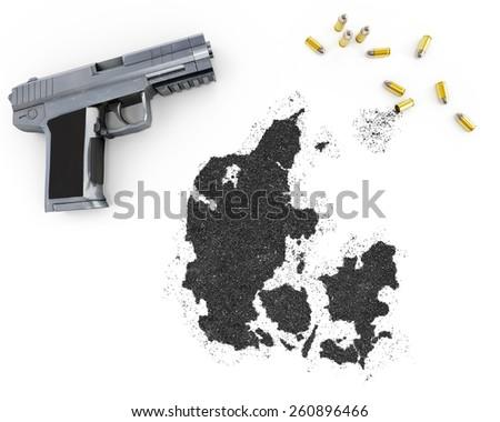 Gunpowder forming the shape of Denmark and a handgun.(series) - stock photo