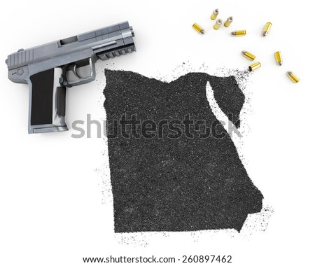 Gunpowder forming the shape of Egypt and a handgun.(series) - stock photo