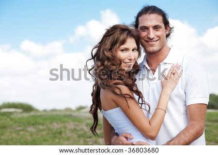 Guy and female embracing on nature background - stock photo