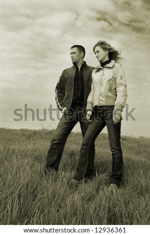 Guy and girl on a spring field. Monochrome - stock photo