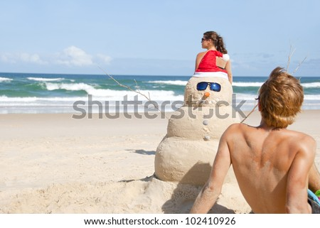 Guy and girl on christmas beach having with perfectly build snowman made out of sand wearing sunglasses. - stock photo