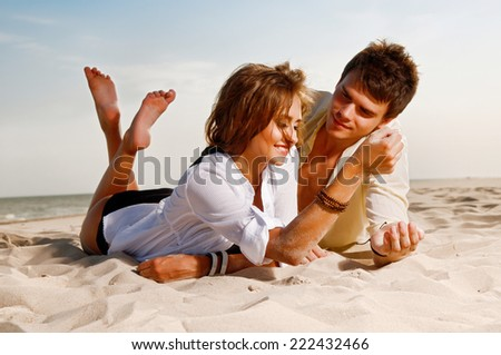 guy and his girlfriend are on the beach - stock photo