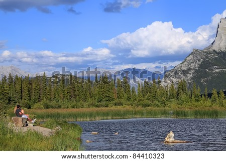 guy and the girl sit on a bench on the bank of lake and looking at mountains