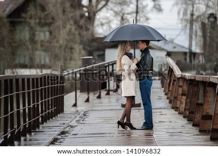 Guy and the girl under an umbrella on a bridge on a cloudy rainy day