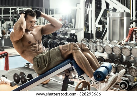 guy bodybuilder , execute exercise on prelum abdominale on bench in gym, horizontal photo - stock photo