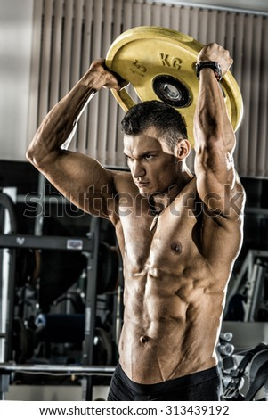 guy bodybuilder , execute exercise with weight in gym, vertical photo