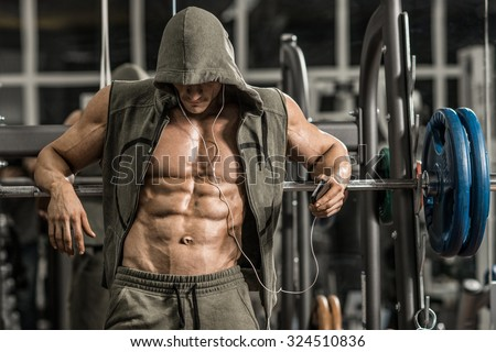 guy bodybuilder tired in gym and listen music with headset  - stock photo