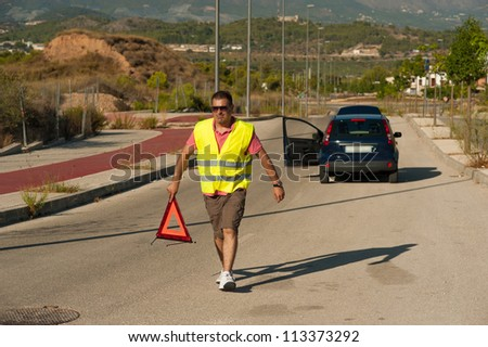 Guy carrying a triangle to warn of his breakdown - stock photo