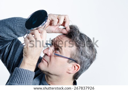 Guy checking out his hair with a mirror - stock photo