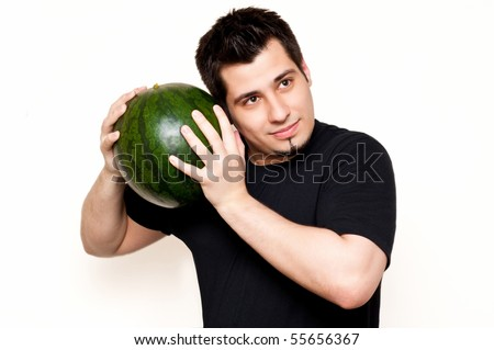 guy checking watermelon for freshness - stock photo