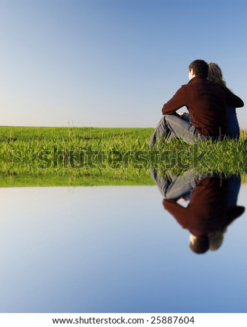 guy embraces girl on a spring field. Near the water - stock photo