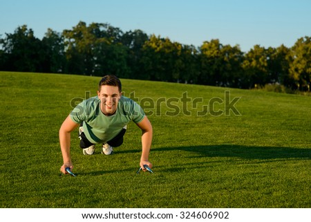 Guy engaged in sports in the park. Guy is wrung in her arms. Healthy lifestyle. - stock photo