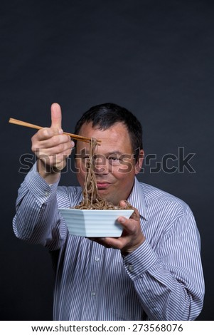 Guy getting pretty fed up with his attempts on eating with chopsticks - stock photo