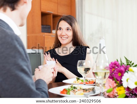 guy gives a ring to his girlfriend during dinner with champagne - stock photo