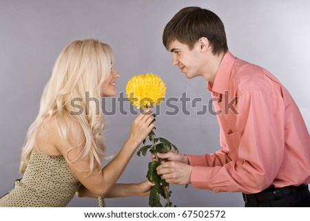 guy gives the girl a flower - stock photo