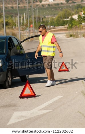 Guy having just broken down on a lonely road - stock photo