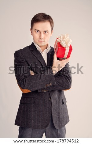 guy holding a gift near the face, a stern look (retro)