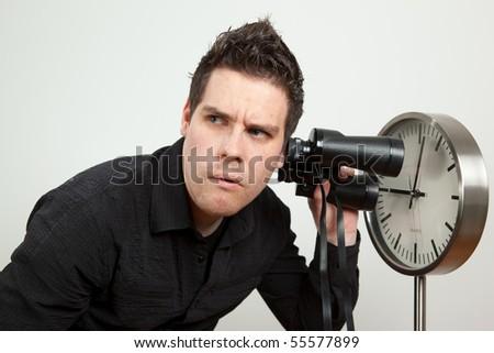 Guy holding binoculars and listening the clock - stock photo