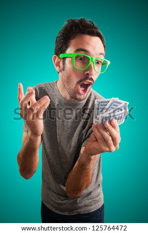 guy holding poker cards on grey background