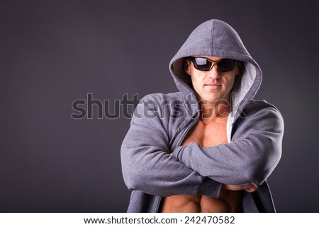 Guy in a sports jacket and sunglasses. Man posing on a dark background, showing muscular body. Sportswear, fitness, bodybuilder. Confident man in sportswear.