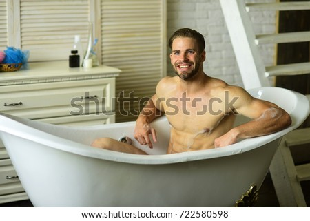 Lovely Guy In Bathroom With Stairs On Background. Sexuality And Relaxation  Concept. Macho Sitting Naked
