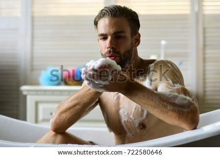 Guy In Bathroom With Toiletries On Background. Macho Sitting Naked In  Bathtub And Playing With