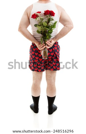 Guy in heart boxers and undershirt holding a bouquet of red roses for Valentines Day behind his back.  Isolated on white.   - stock photo