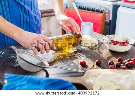 guy in his kitchen preparing dumplings with cherries.He uses a bottle instead of a rolling pin - stock photo