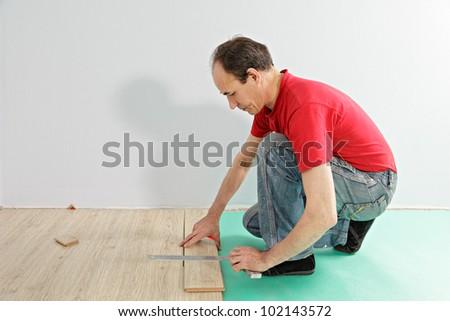 Guy in red shirt measuring laminate plank - stock photo