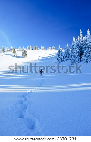 Guy in the distance and line of his footprints in frozen country - stock photo