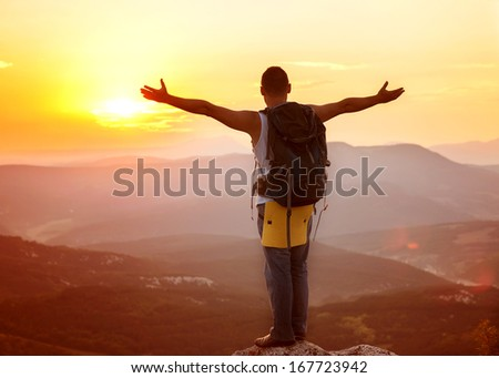 guy in the mountains at sunset. the concept of freedom - stock photo