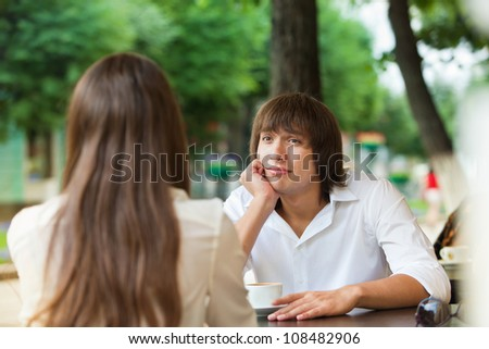 guy is bored on a date with a girl in a summer cafe - stock photo