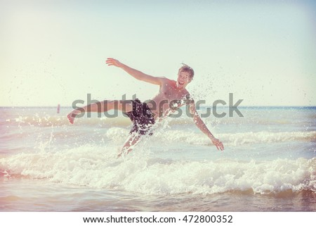 Guy jumping in the waves at the beach, main focus on leg and water drops, Instagram toned