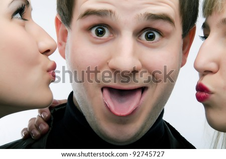 guy kissed by two attractive girls. gradient gray background